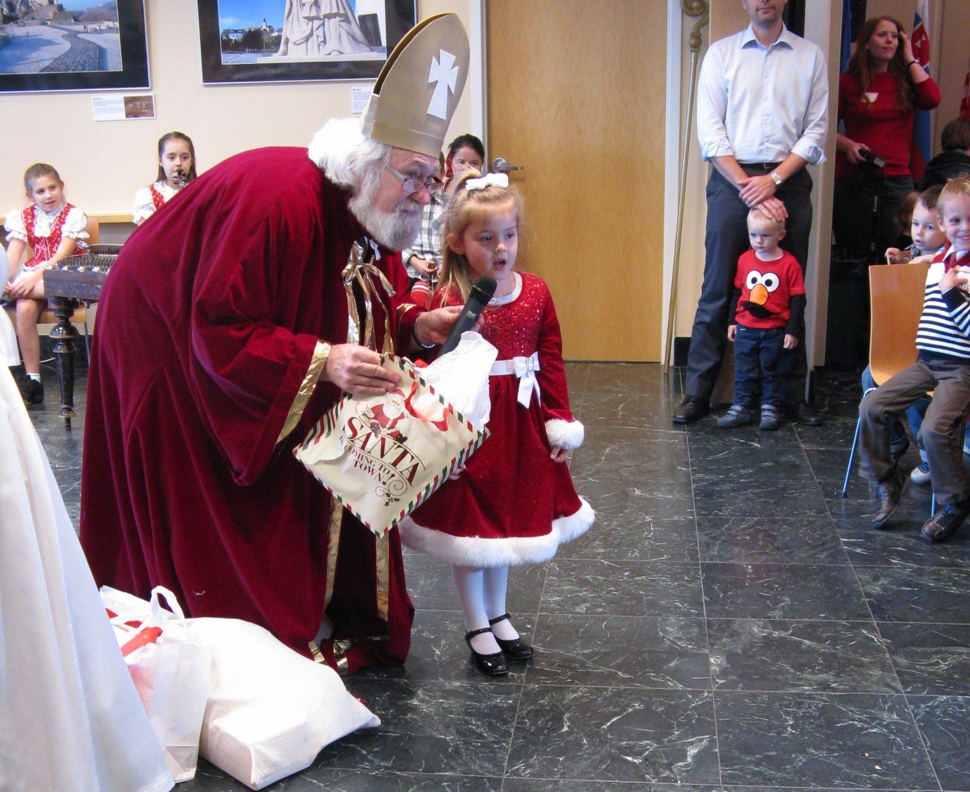 Svätý Mikuláš handing out gifts.